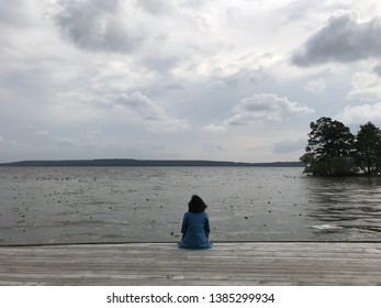 Woman is sitting on a pier over the lake looking at the magnificent view in Sigtuna, Sweden. Woman relaxing near the lake looking at the view. Travel adventure and freedom concept.