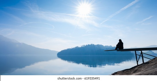 The woman is sitting on the pier. Self reflection. Bright sun in the blue sky.