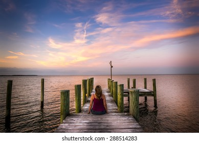 Woman sitting on a pier watching a stunning sunset on the Chesapeake bay in Maryland