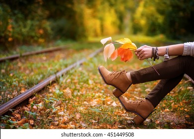 woman sitting on rail trails and holding colorful autumn leaves