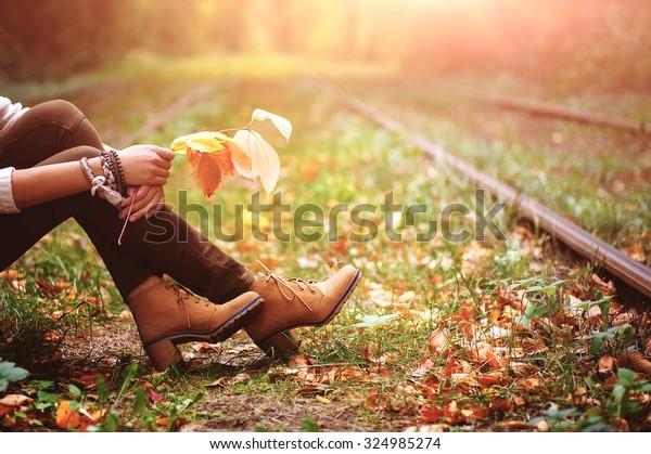 線路の上に座り、色とりどりの紅葉を持つ女性。 自然のビンテージ背景