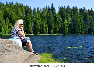 Woman sitting on rock by moraine lake Grosser Arbersee in National park Bavarian forest. Germany.