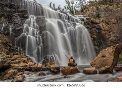woman sitting on a rock in front of Mackenzie Falls