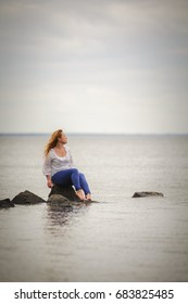 Woman sitting on a rock and looking to the sea