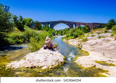 Woman sitting on the rock and painting roman bridge Pont Julien in Provence, France
