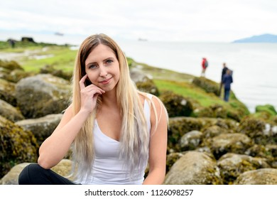 Woman sitting on rock and smiling friendly into the camera in the intertidal zone of Vancouver, British Columbia. Those rocks are underwater at high tide, and out of water at low tide.