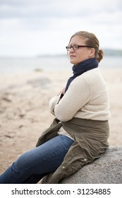 Woman sitting on a rock with a thoughtful expression