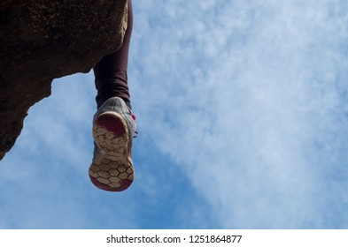 Woman sitting on rock with used running shoes having a break from trailrunning, copy-space on the right.