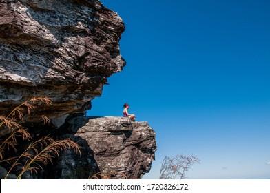 Woman sitting on rock watching nature. Pirenópolis, Goiás, Brazil. May 2015
