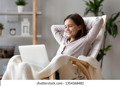 Woman sitting on rocking chair put hands behind head resting on lazy weekend using laptop watching online entertainment programs smiling feels good leisure activities at home modern technology concept