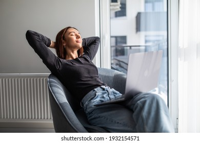 Woman sitting on rocking chair put hands behind head resting on lazy weekend using laptop