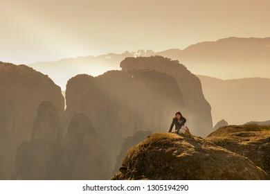 Woman sitting on the rocks of Meteora in Greece.
