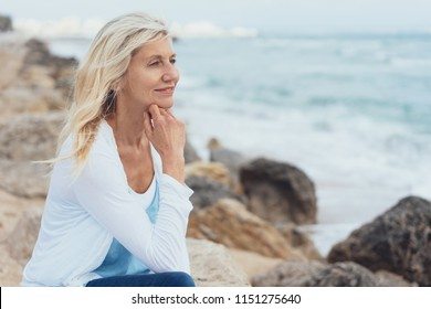 Woman sitting on rocks at the seaside daydreaming with her chin resting on her hand staring into the distance with a smile