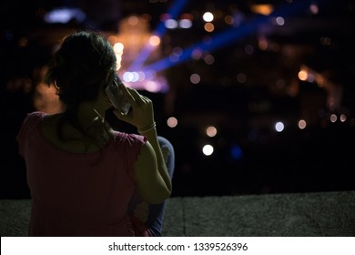 Woman sitting on roof top overlooking city at night talking on phone