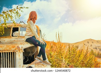 Woman sitting on rusty old classic truck. Young woman in a summer field sitting on old car.