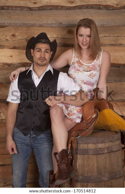 A woman is sitting on a saddle on a barrel next to a cowboy.