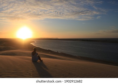 woman sitting on a sandy hill - Shutterstock ID 1902912682