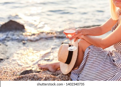 Woman is sitting on sea beach with wineglass of pink wine at sunset in summer vacation in resort. Tourist girl in striped dress with straw hat is enjoying life, relaxing, drinking, traveling.
