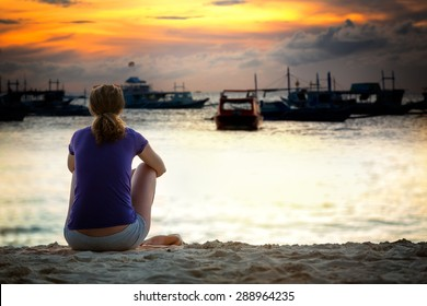 Woman sitting on sea cost and looking in beautiful sunset, back view