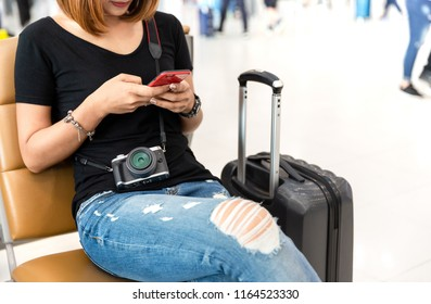 Woman sitting on seat beside baggage and playing phone waiting flight at airport.Travel planning vacation on holiday or summer concept.