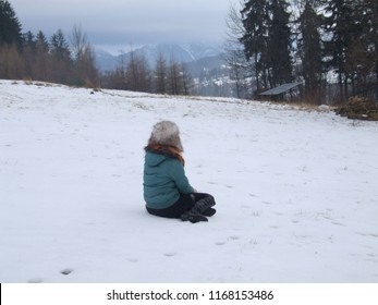 Woman sitting on the snow. Winter season in the moutains scenery. Girl in hat looking at snowy frozen landscape. Cold weather, hiking and relaxing.