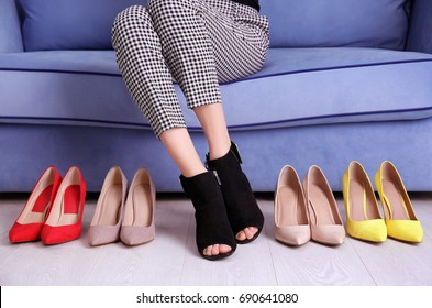 Woman sitting on sofa and choosing shoes at home
