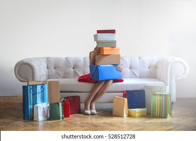 Woman sitting on a sofa, completely covered by shopping boxes and bags