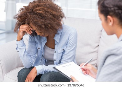 Woman sitting on sofa and crying with therapist taking notes