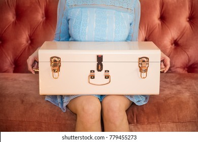 Woman sitting on sofa holding chest box for makeup or jewelry.