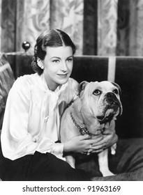 Woman sitting on a sofa holding her bulldog