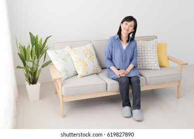 A woman sitting on a sofa, housewife