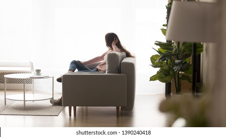 Woman sitting on sofa lost on thoughts enjoy lazy day at home looking out the panoramic window, side view. Modern flat cozy living room interior with comfy couch, laminate flooring coffee table on rug