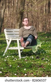 Woman sitting on a sofa in the wood in springtime. She is reading a magazine in the sunlight
