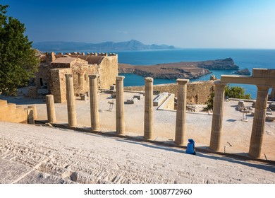 Woman sitting on Staircase of the Propylaea on the Acropolis of Lindos (Rhodes, Greece)