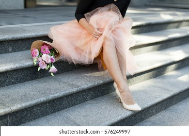 woman sitting on the stairs with flowers tutu skirt legs heel summer