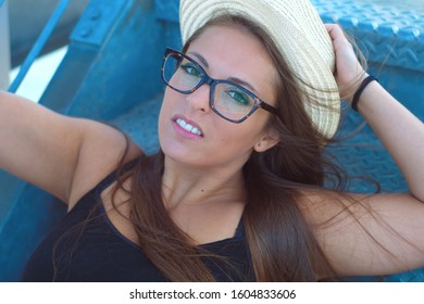 woman sitting on stairs with straw hat and eyeglasses