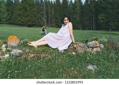 woman sitting on stones and a photographer behind her on meadow