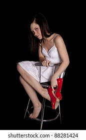 A woman sitting on a stool holding on to her red shoes with a small smile on her face.