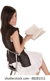 A woman sitting on a stool reading a book and looking over her shoulder with a smile on her face.