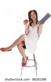 A woman sitting on  a stool with red shoes on holding and reading a book while she holds a fruit in the other.