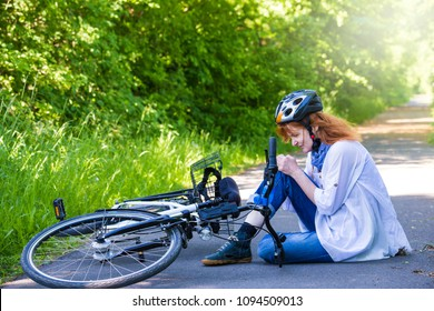 a woman is sitting on the street after a bicycle accident