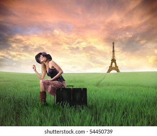 Woman sitting on a suitcase on a green meadow with Eiffel Tower on the background