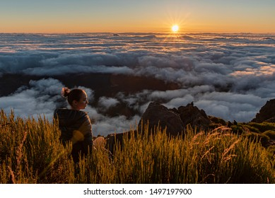 Woman sitting on a summit watching the sunrise over the fluffy clouds
