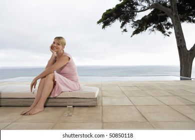Woman sitting on sun bed by infinity pool, portrait