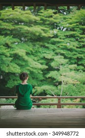 Woman sitting on a temple terrace and looking at a Japanese garden, Kyoto, Japan