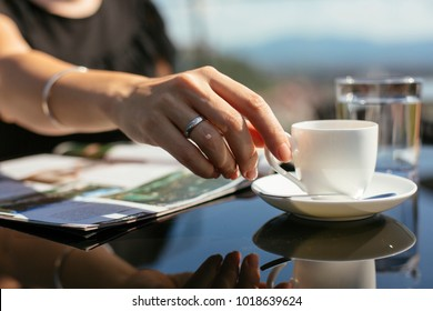 Woman sitting on a terrace drinking coffee. Woman on terrace enjoying sun and reading magazine. Close up shot with coffee cup.