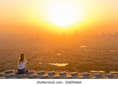 Woman sitting on top of skyscraper overlooking the city at sunrise