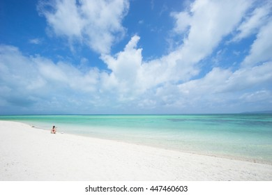 Woman sitting on tropical paradise beach, Taketomi Island, Okinawa, Japan