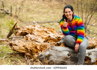 Woman sitting on trunk tree and giving thumb up