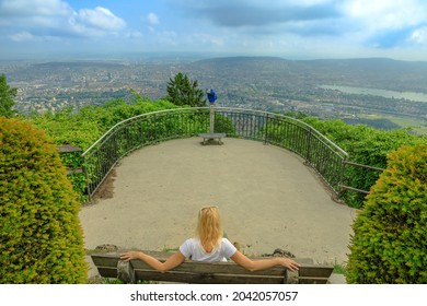 Woman sitting on Uetliberg mountain lookout. Zurich skyline on a Swiss on Uetliberg mountain in the Swiss plateau in Switzerland. Carefree girl with looking panorama of Zurich city and its lake.